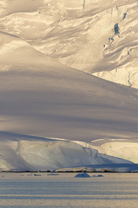 Close up of a sunlit, snowy cliff along the coast