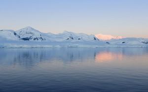 Sunlit, snowy coast at dawn