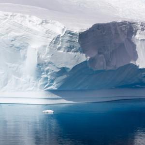 Sunlit, towering iceberg in deep blue waters