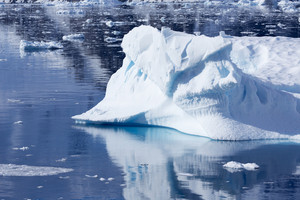 Sunlit iceberg in icy waters