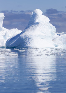Close up of sunlit icebergs in icy waters