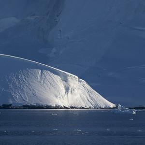Sunlit iceberg and a snowy coast