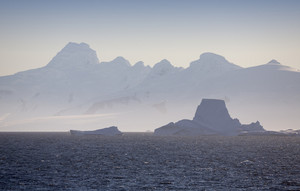 Icebergs and a snowy coast silhouetted under thick fog