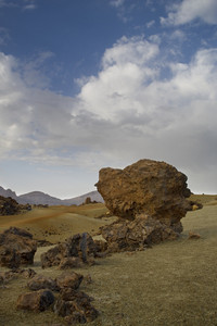 Rock formations in a sandy desert under a cloudy sky