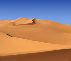 Desert sand dunes under a blue sky