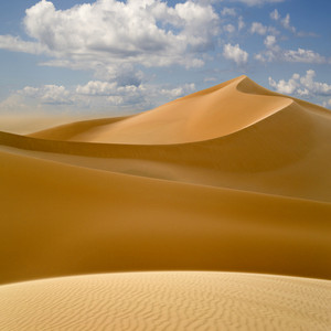 Wind-patterned desert sand dunes under a blue cloudy sky