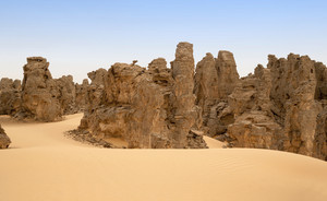 Rock formations in a sandy desert at dawn