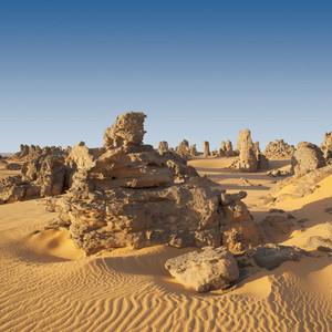 Rock formations in a sandy desert under a blue sky