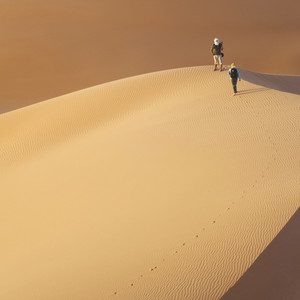 Travelers atop a sand dune in the desert