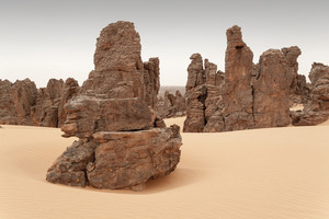 Rock formation in a sandy desert under a grey sky