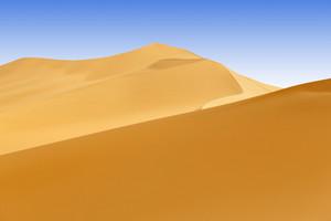 Sand dunes in the desert under a blue sky