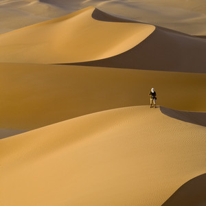 Photographer atop a sand dune in the desert