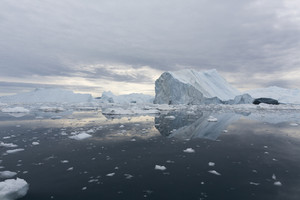 Iceberg and ice chunks under a stormy sky