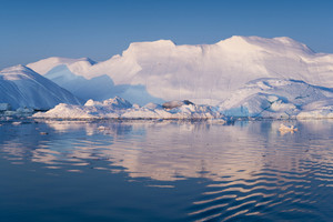 Towering, sunlit iceberg in calm water