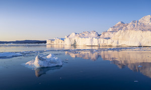 Sunlit iceberg and ice floe reflected in the water