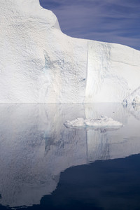 Sunlit iceberg reflected on the water under a blue sky