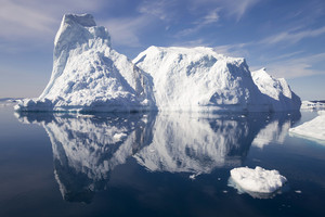 Sunlit iceberg reflected on rippled water under a blue sky