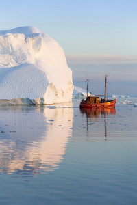 Red boat traveling by a sunlit iceberg at dusk
