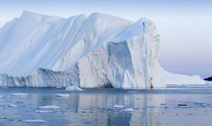 Towering iceberg floating in deep blue water