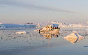 White boat traveling past sunlit icebergs