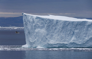 Sailboat traveling past a towering iceberg