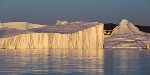 Towering iceberg bathed in golden sunlight