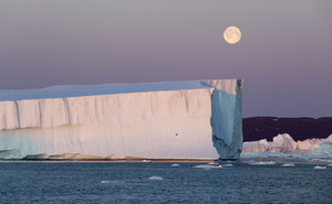 Moonlit icebergs against a full moon
