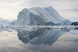 Towering iceberg reflected in still, icy waters