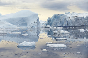 Towering icebergs reflected in icy waters under a grey sky