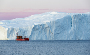 Red boat traveling past an iceberg at dawn