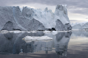 Towering iceberg reflected under a grey sky