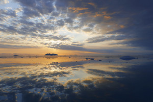Clouds reflected in the ocean during a golden sunset