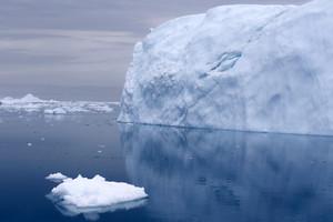 Iceberg reflected under a grey sky