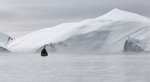 Boat traveling past an iceberg on a foggy day