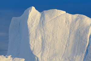 Close up of an iceberg cliff against a clear blue sky