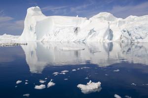 Sunlit iceberg in deep blue, icy water