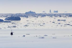 Boat traveling past sunlit icebergs at dusk