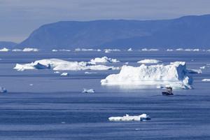 Boat traveling past sunlit icebergs along the coast