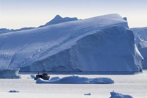 Boat traveling past a sunlit iceberg