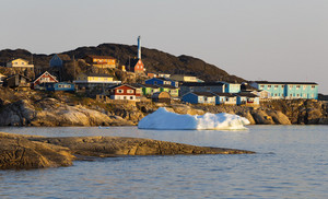 Sunlit iceberg by a village on the coast