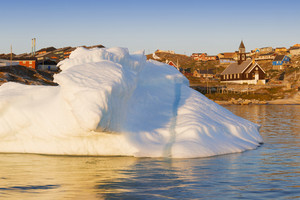 Sunlit iceberg by a village on the coast