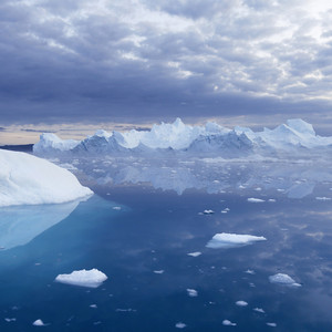 Towering iceberg reflected under a cloudy sky