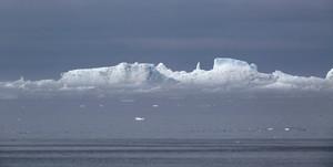 Iceberg under a grey sky and heavy fog