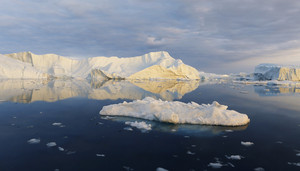 Sunlit iceberg and ice floe reflected in deep blue water