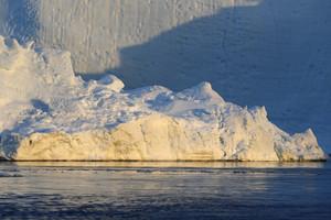 Sunlit iceberg in deep blue water