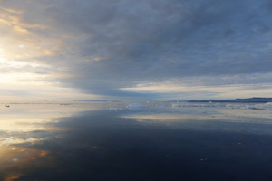 Cloudy sky reflected over the icy ocean at sunset