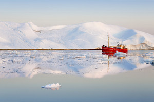 Red boat traveling past an iceberg in icy waters at dawn