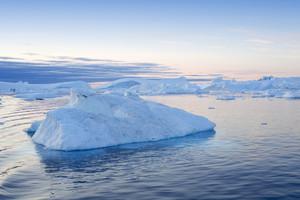 Iceberg and ice floe at dusk