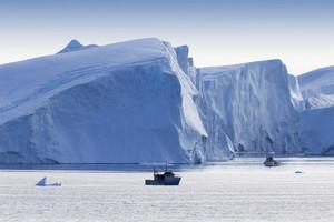 White boat traveling past a sunlit iceberg