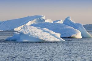 Sunlit icebergs under a foggy sky